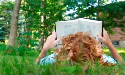 redhead child reading book in grass