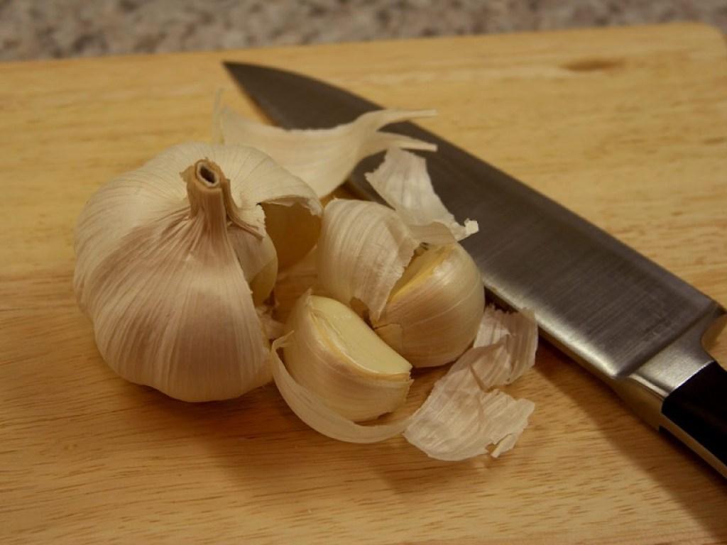 garlic on cutting board with knife