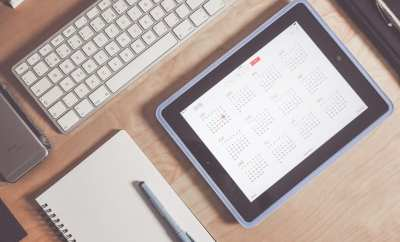 tablet and planner on table for planning when to go to the doctor