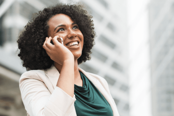person talking on phone and smiling to secure an interview miss millennia magazine
