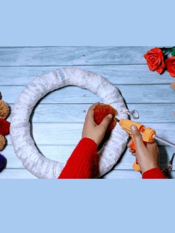 How do you make wool felt pom poms. We start to glue the pom poms on the cardboard wreath