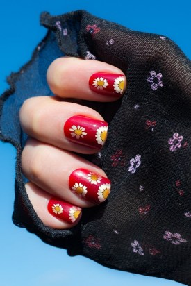 Red nails with daisy flowers