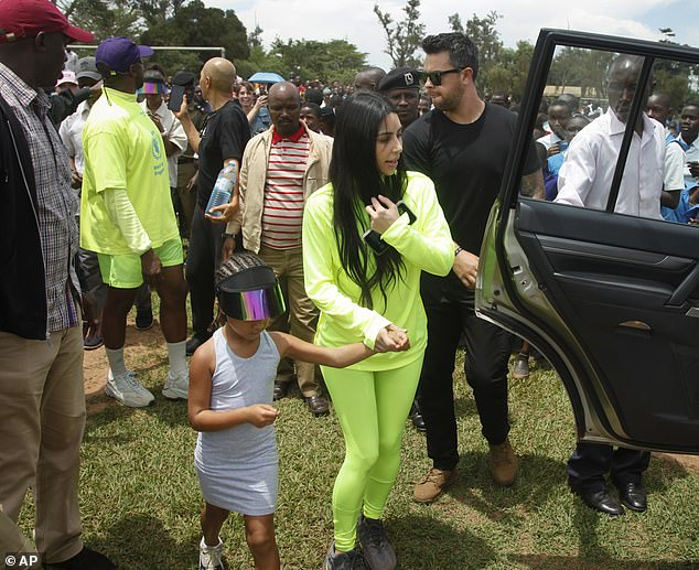 Kim Kardashian and Kanye West twin in neon outfits in Uganda