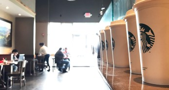 Starbucks is busy with people studying and mingling.