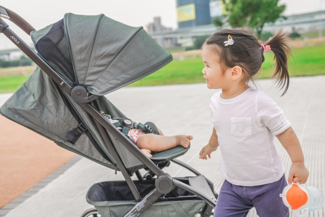 A young child pushing a stroller  Description automatically generated with medium confidence