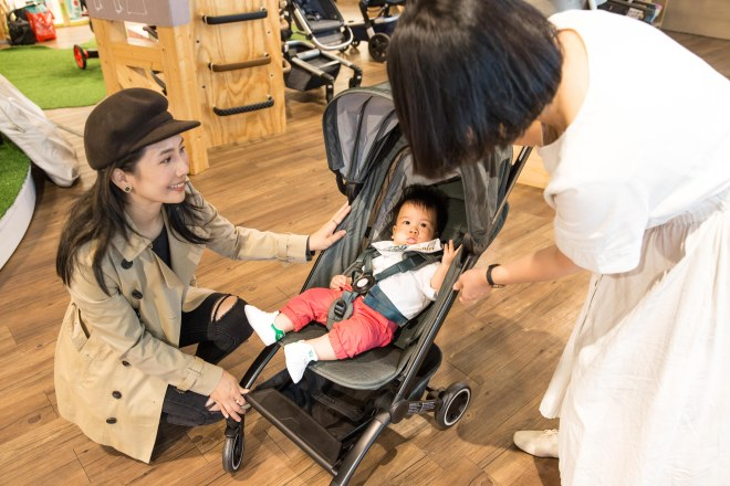 A person pushing a baby in a stroller  Description automatically generated with medium confidence