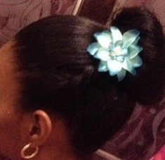 Step 5: Sometimes, I got a step further and add a small floral embellishment to the side of my bun, in line with the twist, such as this teal flower with rhinestone embellishment at the centre.