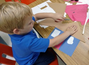 Young boy gluing cut paper to make a house