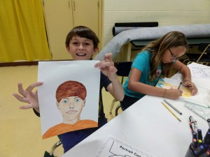 Boy holding up a self portrait while sister is still drawing beside him