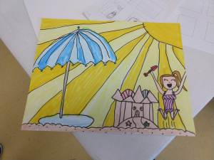 Marker drawing of a beach with umbrella, sandcastle, and girl cheering