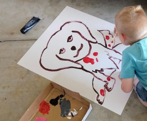 Boy painting a huge puppy on a poster board