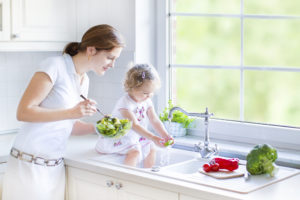 Mother and daughter in kitchen with big garden view window