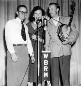 "Mr. O. D. ""Cal"" Calhoun, the beloved emcee for Carolina Barn Dance, is pictured with Lulu Belle and Scotty Wiseman on the stage at the Carolina Theater in Spruce Pine. After a national musical and screen career, the Wisemans return to their mountain home near Spruce Pine in the late 1950's. Scotty farmed and Lulu Bell served two terms in the North Carolina Legislature becoming the first Democrat and woman to fill the position from the district."