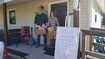 Larry Davis and Tablitha Callahan pose with food boxes at the door of the Mitchell County Shepherd's Staff