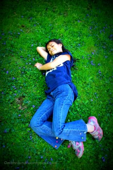 My 10 year old daughter resting on a carpet of grass and violets
