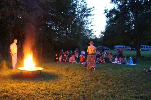 My husband reading stories by the campfire to cub scouts