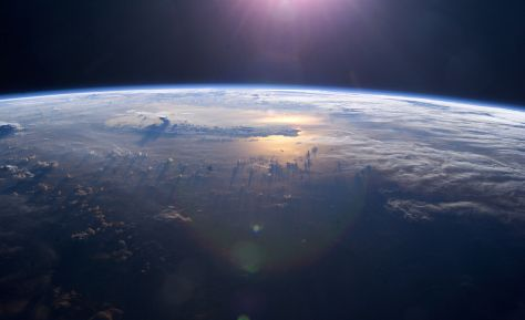 Recent view of the Pacific Ocean from the International Space Station. Although plenty un thunderheads and storm clouds are seen aloft, we can also glimpse the so-called 'peaceful' ocean as the setting sun reflects upon its surface through a clearing in the clouds