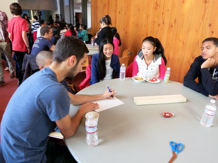 Mentor and MITES '11 alum Andrew Berta sketched ideas for his team's prosthesis as mentees Rachel Lee, Annie Miao and Miles Graham offer suggestions.