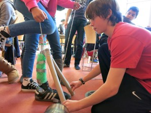 Mentee Dante Greco-Henderson aligns the cardboard tube supports his team implemented for their prosthesis.