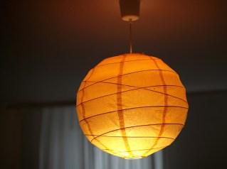 Mit dem orangen Lampenschirm wirkt das Zimmer wärmer und gemütlicher.