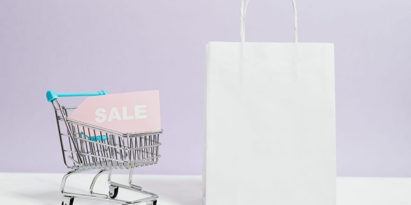 Sale sign in a miniature shopping cart and paper bag