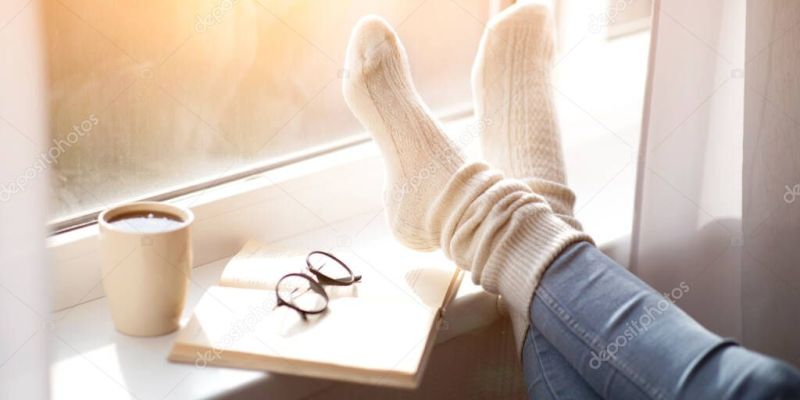 Cropped view of woman putting her feet in warm comfy socks on windowsill with book and coffee, closeup