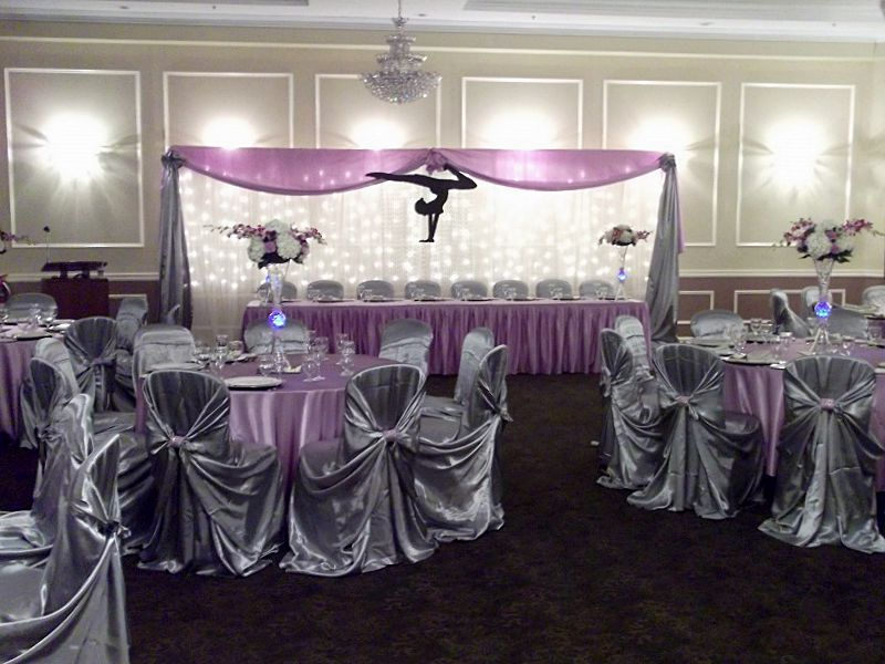 The purple and silver theme played well on the dais and guest tables at this wedding reception