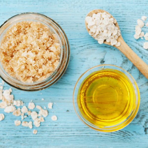 """Rich results on Google's SERP when searching for """"organic body scrub"""" sugar scrub in a bowl with salt sprinkled around the bowl on a blue board with spoon and organic oil"""