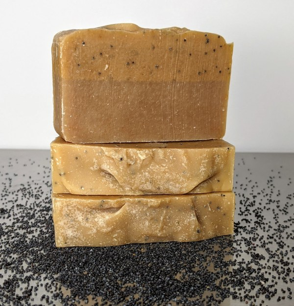 three bars of lemon poppy seed handmade organic soap with poppy seeds on the table scented with vanilla, citrus, lemon essential oils for brightening skin and removing odors