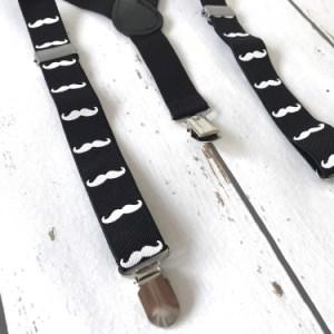 Een leuke zwarte bretel met witte snorretjes.