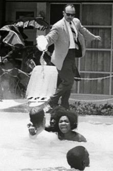 En 1964, el gerente de un hotel vierte acido en la piscina mientras varias personas de color se encuentran nadando