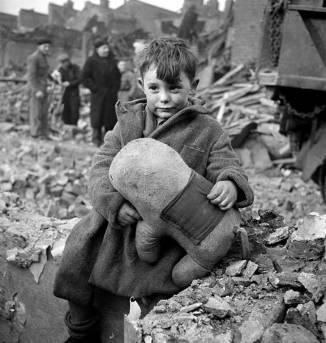 Niño sosteniendo su juguete en medio del desastre en 1945