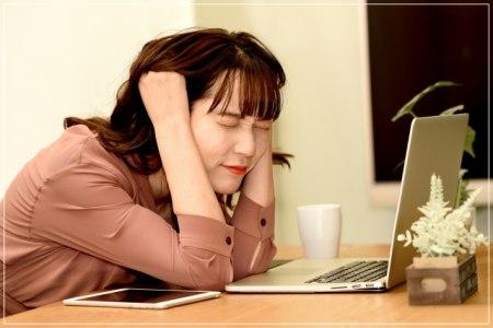 頭を抱えるオンライン授業をする学生の画像