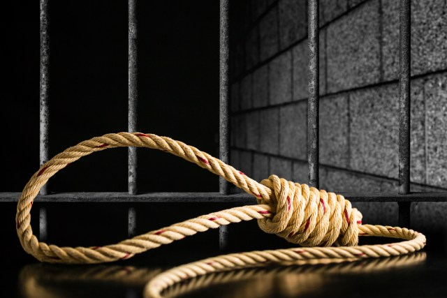 Brown rope noose dark and light on black table with old prison bars cell lock background dark black and light