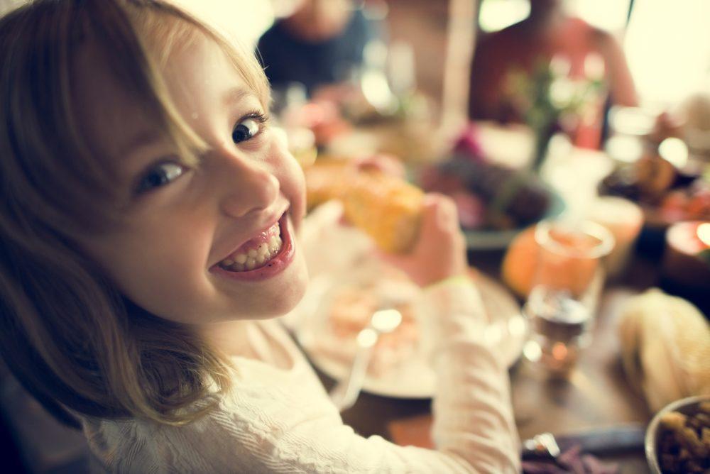 Little Girl Eating Corn Thanksgiving Celebration Concept