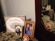 The Capodimonte Rose from my father is displayed on my dresser with a picture of my parents.