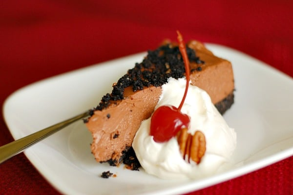 A slice of rich and easy no-bake chocolate cheesecake is ready to serve. | mjbakesalot.com