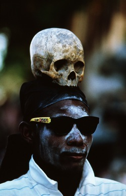 On a street in Port au Prince, during the Day of the Dead a man walks among the crowds with a scull on his head. Ghede is Death.  He is smiling, affable, loves to party, he is often called BARON SAMEDI. In this aspect he is DEATH. Ghede is a clown, an interrupter, a coarse fellow. But he is history too. As keeper of the cemetery he has intimate contact with the dead. He knows what their plans were, what's going on in families, what the connections of things are. And he is quite generous with his information. Even when he is clowning or performing his erotic antics, if you can pull him aside and ask him a serious question you will get a serious and reliable answer.