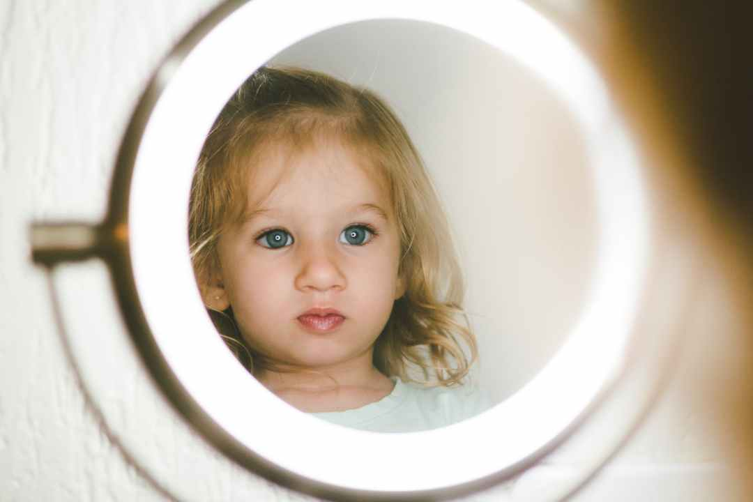 selective focus photography of girl facing lighted magnifying lamp