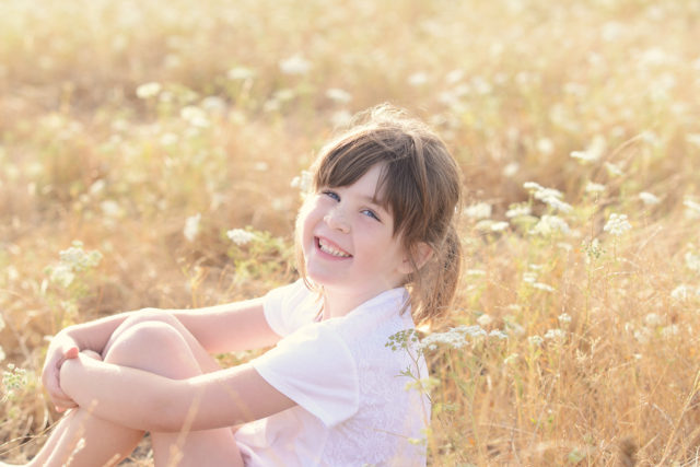 smiling child in field of flowers