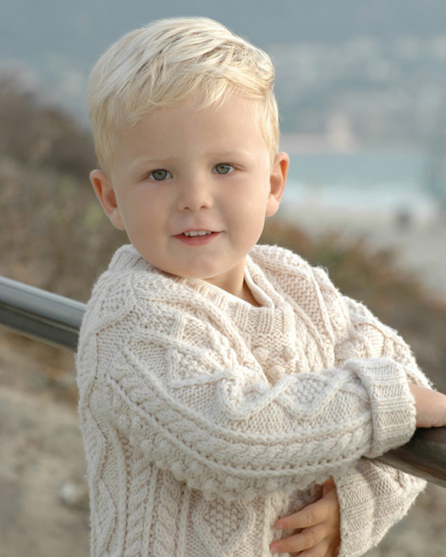 little boy in sweater at the beach