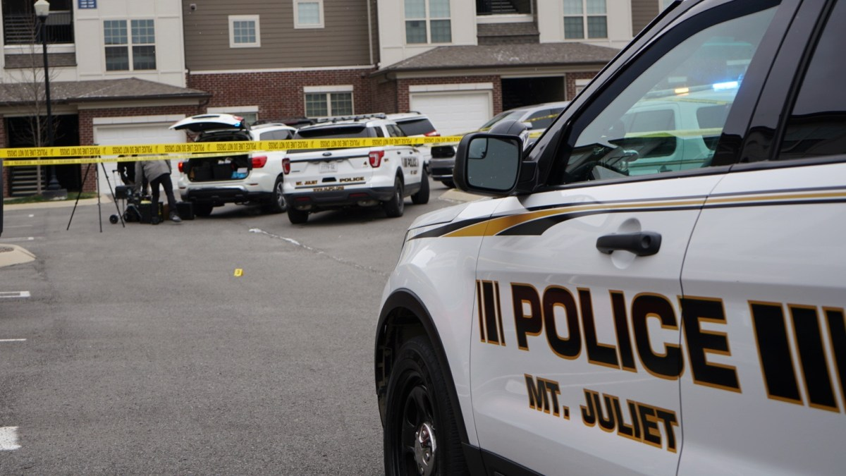 Photo of Shooting Scene with Crime Scene Tape and Police Vehicles