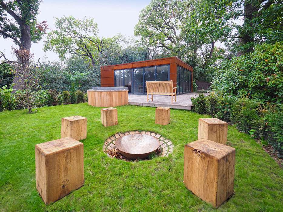 firepit in garden landscaping design with wooden block seats, hot tub and garden room