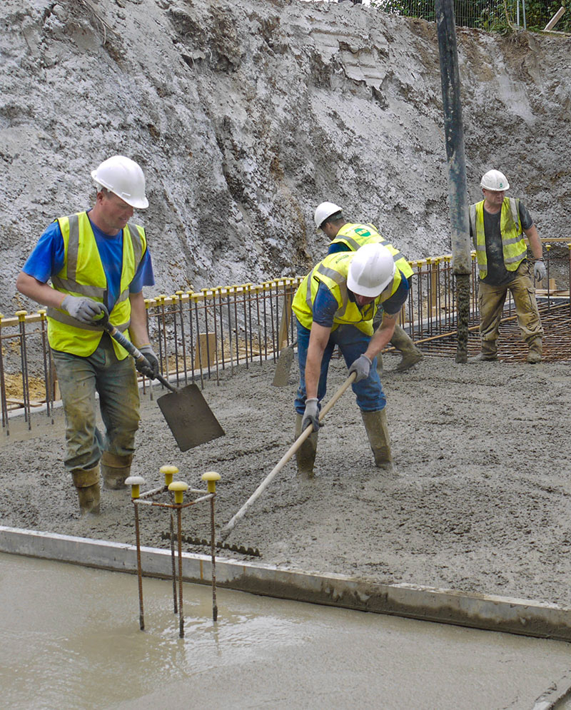 Concrete slab basement foundations for a house being poured by a groundworks gang