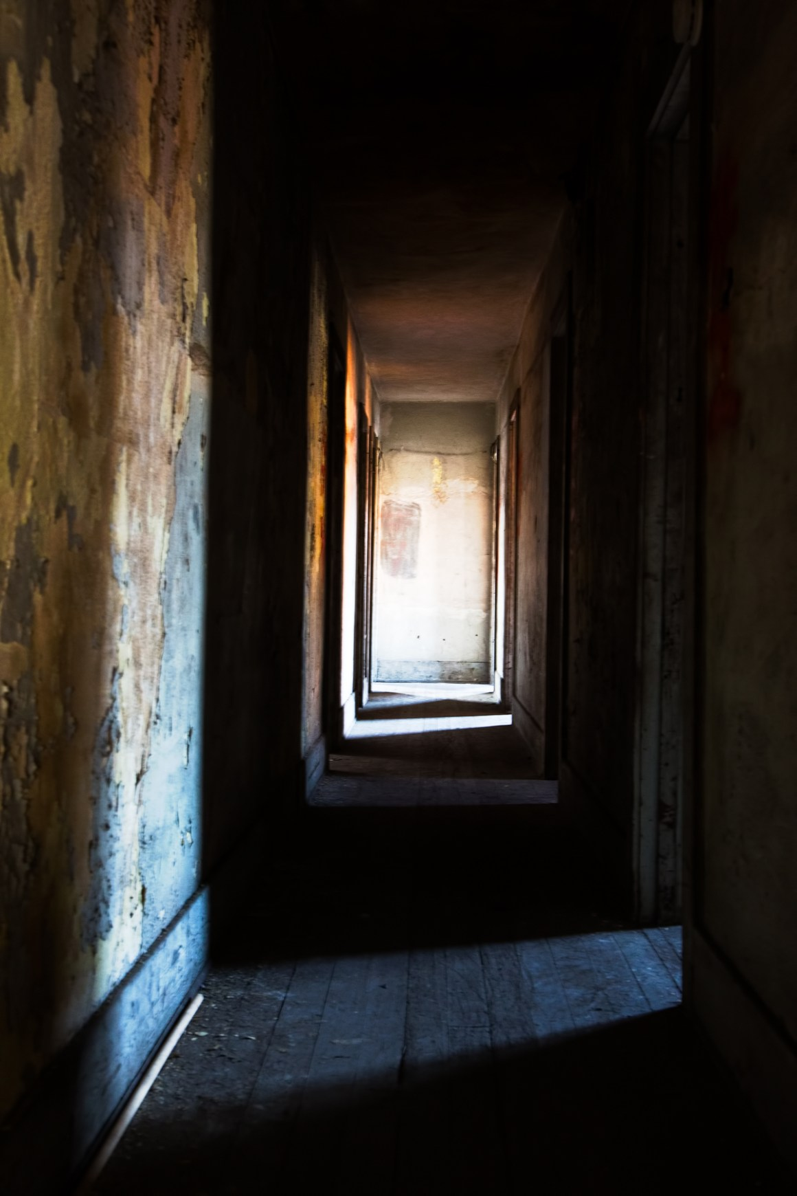 Hallway old building urban decay moody lighting muted colors photograph