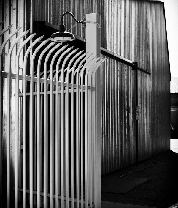 Black and White photo repeating Lines urban landscape coregated metal building with white fence