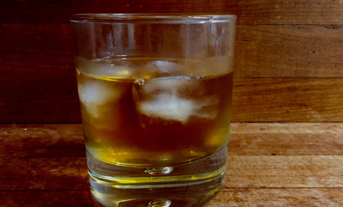 whiskey with ice on a wood counter
