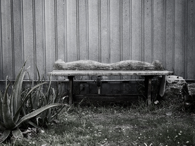 desaturated photo with weathered wooden bench