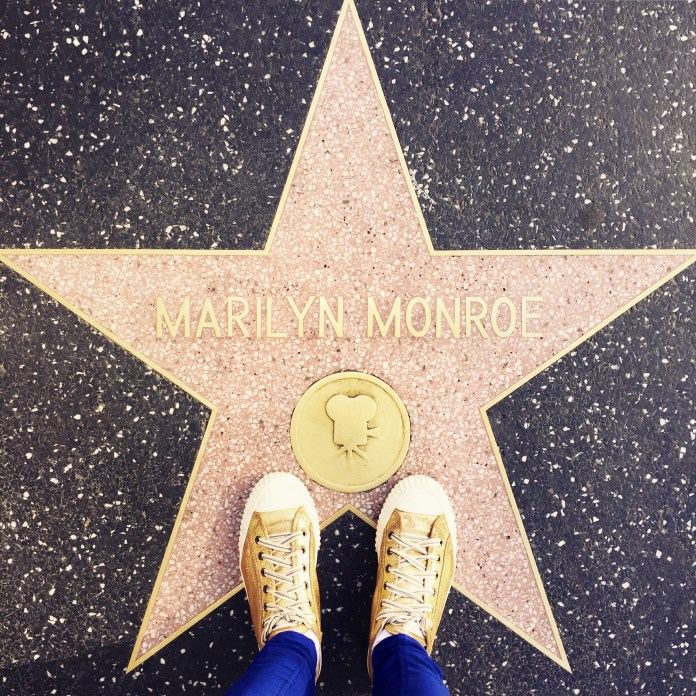 Los Angeles, United States - December 22, 2014: The Walk of Fame in Hollywood.  A girl standing with her All-Star's on the star of Marilyn Monroe for the photo.