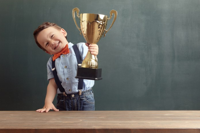 A cute, smiling 2-3 years old boy is standing behind a wooden table and raising a golden trophy with his hand.  Little boy is wearing an orange bow tie and blue trousers with suspenders.